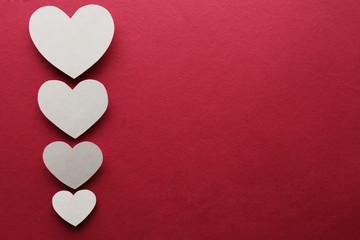 White paper hearts on dark pink background