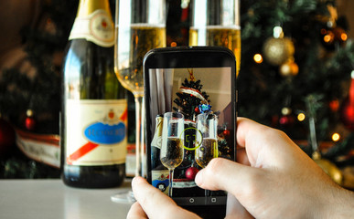 Hand taking photo of Christmas tree and champagne glasses by smartphone