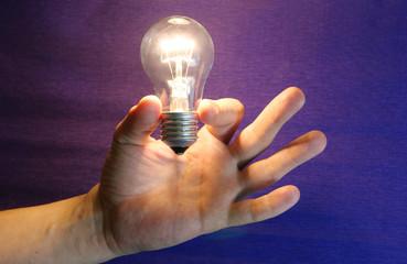 Рука держит пальцами горящую электрическую лампу накаливания синий фон