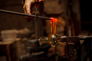 Glass Artist in her workshop making glassware