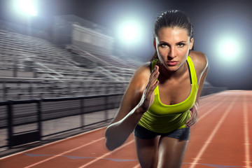 Female runner sprinter exercising and training intense track and field athlete determination for greatness in sports