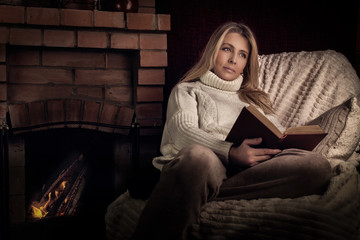 Женщина у камина читает книгу