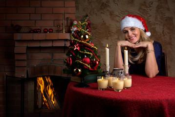 Женщина рядом с камином в шапке Санты и елкой