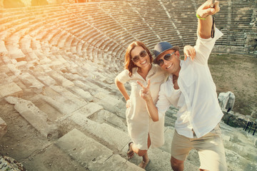 Happy couple take a selfie photo on the steps of antique ruins
