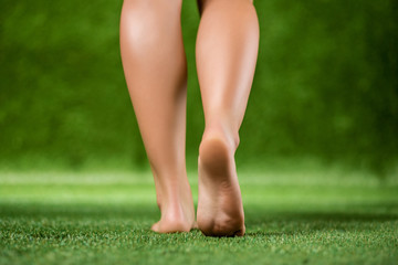 His bare feet beautiful woman close up on a grass.