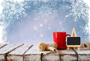 Cup of hot coffee and cozy knitted scarf and blackboard on wooden table in front of glitter background