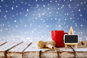 Cup of hot coffee and cozy knitted scarf and blackboard on wooden table in front of glitter snowy background