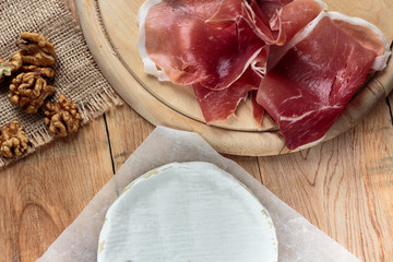 Camembert and prosciutto on old rustic wooden table