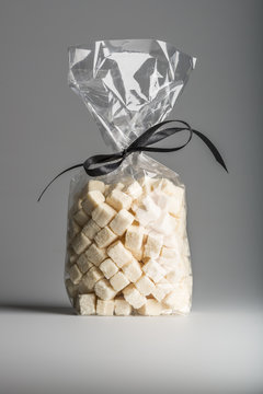 Luxury bag of dried coconut cubes isolated with elegant ribbon