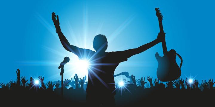 Concept du concert de musique rock avec un chanteur qui salue son public en brandissant sa guitare et la foule qui l'applaudit à la fin du spectacle.