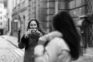 Beautiful woman taking a picture of her friend with a vintage camera