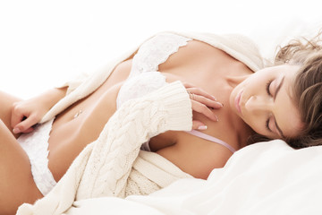 Young beautiful women in underwear is sitting on the bed in the morning