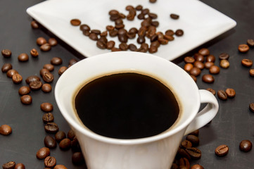 cup of coffee and saucer with coffee beans on blackboard