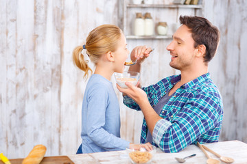 Positive father and daughter having breakfast