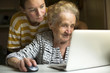 Mature woman learns from the granddaughter to work on the computer.