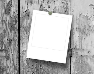 Single square empty photo frame with pin on grey wooden window background