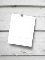 Single square empty photo frames with pin on light grey wooden boards background