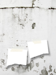Two ripped piece of paper with scotch tape on grey scratched and cracked plastered wall background