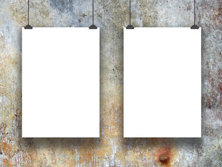 Two hanged paper sheet frames with clips on blue and brown concrete wall background