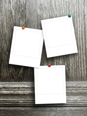 Three square empty photo frames with pins on dark brown wooden boards background