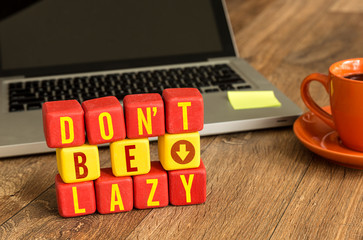 Don't Be Lazy written on a wooden cube in a office desk