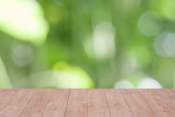 Wood table top on bokeh abstract green background - can be used for montage or display your products