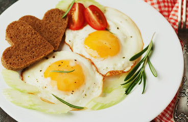 Fried eggs with fresh vegetables and toast in shape of heart on white plate, delicious Breakfast