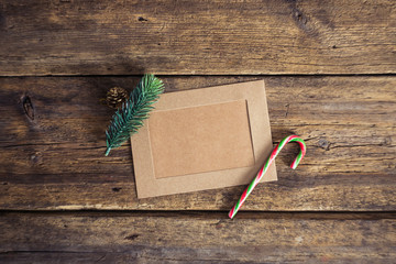 Christmas card on a wooden background with a candy cane, fir branches