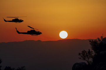 Two flying army helicopters on sunset background
