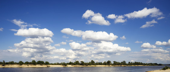 White clouds above the river .