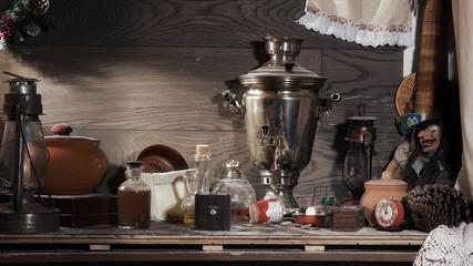 На старом чердаке. Натюрморт. Множество разных старых предметов - часы будильник, керосиновые лампы, самовар, сломанные игрушки, коробки и шкатулки. Бутылки, кастрюли. Много пыли.
