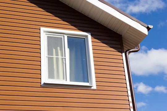 window in wall of brown vinyl siding