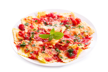 plate of ravioli with tomato sauce on white background