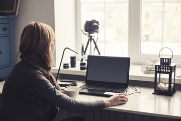 Workplace with open laptop with black screen  on modern wooden desk, angled notebook on table in home interior, filtered image.