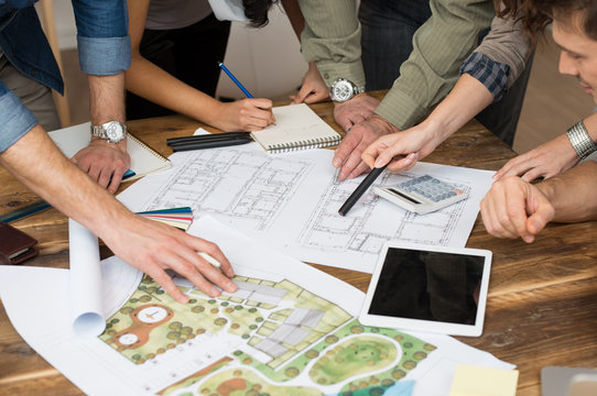 Architect team discussing on blueprints