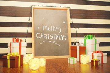 Merry Christmas inscription on picture frame with gift boxes and