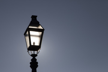 Old street lamp on a background of dramatic dark blue skyBacklight. Highlights sun. Space for text