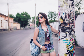 Young sexy woman portrait. Stylish hippie girl posing on the street with interested bohemian look. Vintage lifestyle trendy portrait. Photo toned style Instagram filters.