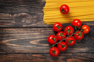 Spaghetti and tomatoes on an old  vintage wooden table