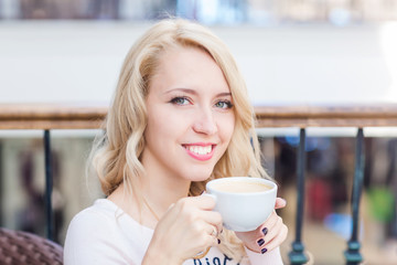 Beautiful young girl drinking coffe in a restaurant.