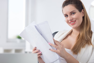 Smiling office worker holding documents