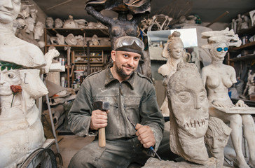 Sculptor man working in his workshop