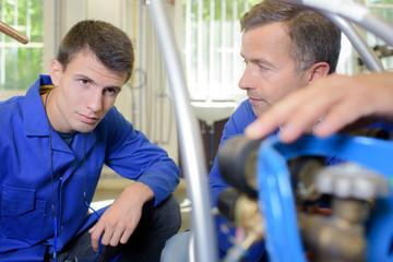 Man explaining controls of gas bottle to apprentice