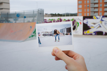 Hand holding her polaroid doing skate