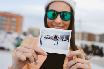 Smiling girl holding her polaroid doing skate