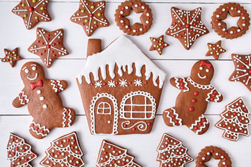 Gingerbreand cookies christmas composition, house man and woman couple, stars, fur trees on white wooden table background. New year traditional dessert food. Top view