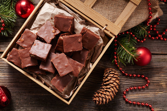 Christmas fudge traditional homemade chocolate sweet dessert food in wooden box on vintage table background. Top view. Delicious unhealthy snack