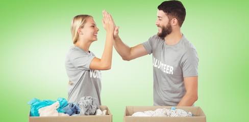 Composite image of happy volunteer doing high five