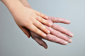 Hands of young child and old woman