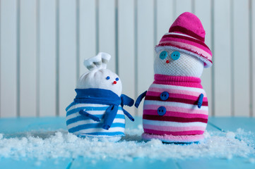 Couple of Hand Made Snowman with striped sweaters on wooden background